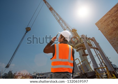 stevedore or foreman, engineering, loading master talks to crane driver by walkie talkie for safety lifting  the goods shipment, lifting by gantry crane, working at risk on the high level insurance  #1320659597