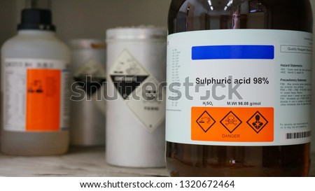 Bottle of Sulfuric Acid, H2SO4 with Properties information and its chemical hazard warning symbols. Corrosive hazard symbol, Inhalation hazard symbol and Toxic symbol #1320672464