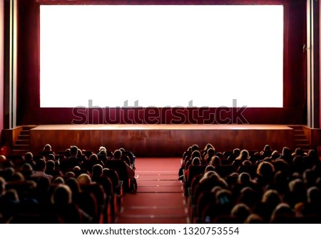 People in the cinema auditorium with empty white screen. #1320753554
