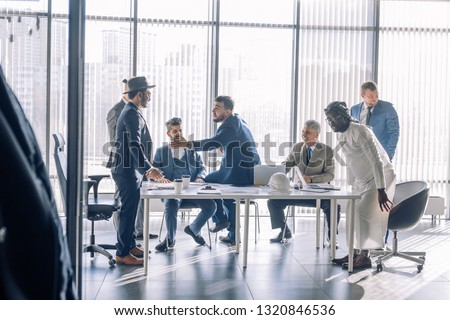 Diverse business executives discussing project sitting at conference table, multiracial partners talking about marketing plan at corporate briefing, african manager offering new idea at group meeting #1320846536