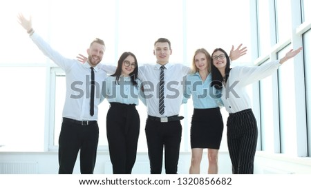 group of young professionals standing near the office window #1320856682