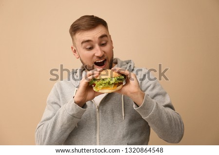 Young man eating tasty burger on color background #1320864548