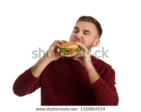 Young man eating tasty burger on white background #1320864554