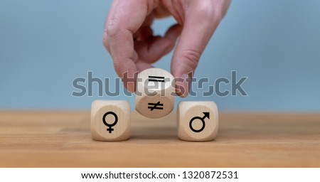 Symbol for gender equality. Hand turns a dice and changes a unequal sign to a equal sign between symbols of men and women. #1320872531