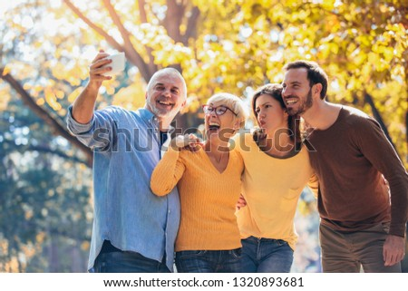 Smiling family on an autumns day in park make selfie photo.