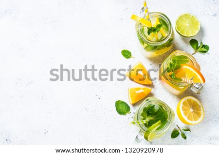 Lemonade set. Lemonade, mojito and orange lemonade. Iced summer drink in mason jar with ingredients on white table top view. #1320920978