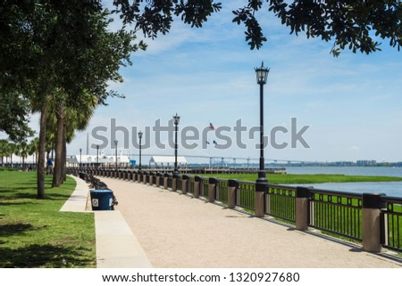 Asphalt path in the park along the bay. Walkway in the summer park with lanterns and green trees near the ocean. Joe Riley Waterfront Park. Charleston, SC / USA - July 21 2018 Royalty-Free Stock Photo #1320927680