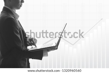 Business man using laptop with abstract financial chart and up trend line graph in stock market on black and whit color background #1320960560