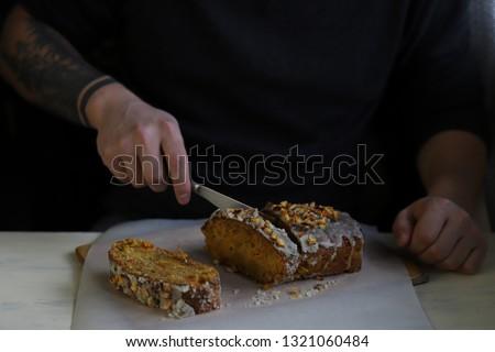 A tattooed man cuts apricot vegan cake  #1321060484