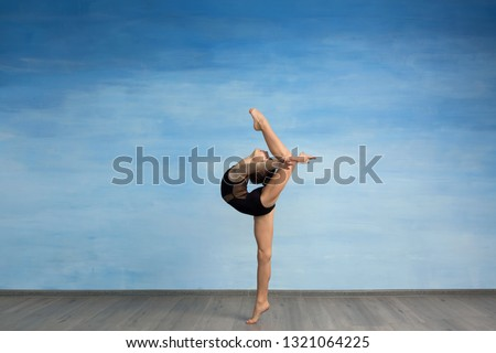 A young girl in a black gymnastic swimsuit gymnast makes an exercise standing backward and legs in semi splits on a blue background. A young girl gymnast performs kick back arms straightened back #1321064225