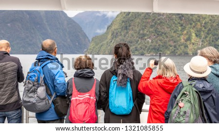 Tourists enjoy the mountains, water and clouds of Doubtful Sound from a tour boat in Fiordland National Park, New Zealand.