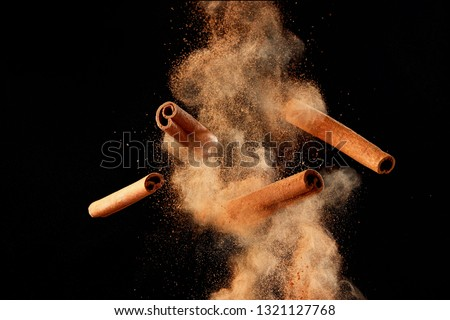 Food explosion with cinnamon sticks and powder, on black background. Royalty-Free Stock Photo #1321127768