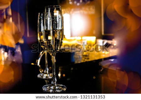Two glasses of champagne on black stylish background with golden bokeh circles. #1321131353