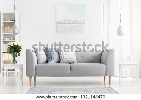 Flowers on table next to grey settee with pillows in apartment interior with poster and lamps. Real photo #1321146470