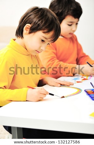 two adorable happy children drawing with crayons #132127586