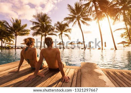 Couple enjoying beach vacation holidays at tropical resort with swimming pool and coconut palm trees near the coast with beautiful landscape at sunset, honeymoon destination #1321297667