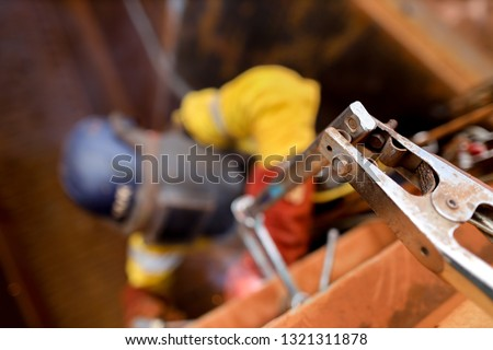 Pic of using earth ground connector with unfocused rope access abseiler welder welding safety helmet protective shield equipment while performing hot work difficult task background construction site