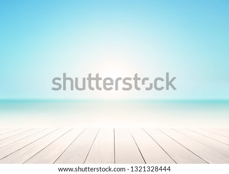 The blur cool sea background with wood floor foreground on horizon tropical sandy beach; relaxing outdoors vacation with heavenly mind view at a resort deck touching sunshine, sky surf summer clouds.
