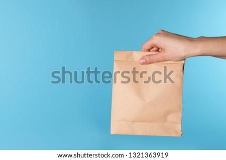 Woman holding paper bag on color background. Mockup for design #1321363919