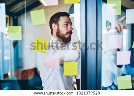 Pensive caucasian proud ceo dressed in white shirt pointing on colorful stickers with text notes glued on glass wall.Concentrated bearded entrepreneur brainstorming while standing in office interior #1321379528