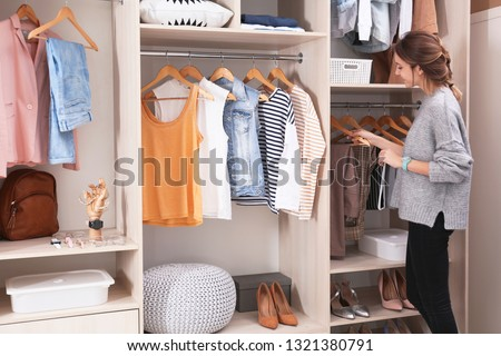 Woman choosing outfit from large wardrobe closet with stylish clothes, shoes and home stuff #1321380791
