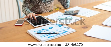 A business woman is writing a summary of her business spending items. Women are recording their own income-expense accounts using laptops. #1321408370