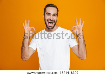 Image of joyful guy 30s with beard and mustache showing ok sign while standing isolated over yellow background #1321418309