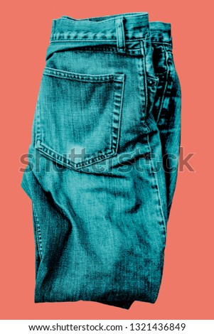 Blue Jeans, half folded isolated and digital dyed with green colour, showing a back pocket on coral colour background. #1321436849