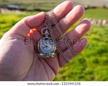 One person with one antique chain watch plated in his hand #1321441136