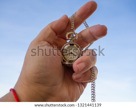 One person with one antique chain watch plated in his hand #1321441139