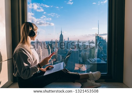 Blonde hair female blogger listening to music in headphones during freelance work on laptop computer. Hipster girl traveler enjoying panoramic view of New York downtown and studying with audio book #1321453508