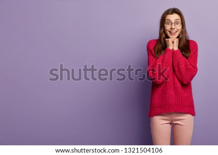 Half length shot of attractive pleased female model keeps hands under chin, gazes with eyes full of happiness, dressed in red jumper and trousers, models over purple background with free space #1321504106