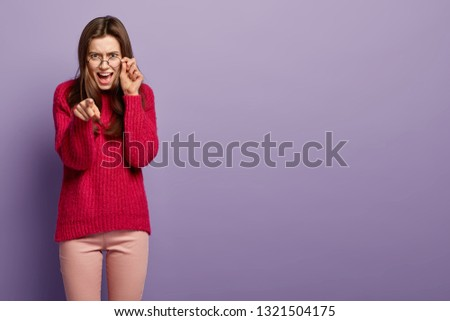 I blame only you. Outraged European woman keeps hand on frame of spectacles, points angrily at camera with forefinger, disappointed by big mistake, dressed in red jumper, isolated over purple wall #1321504175