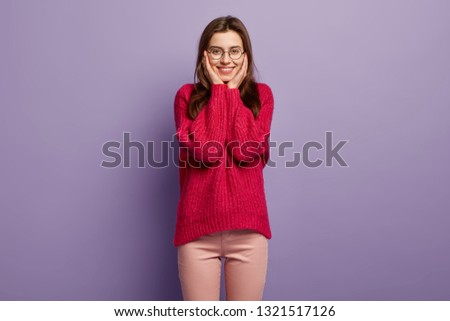 Indoor shot of cheerful female model holds hands on cheeks, gazes with happiness, dressed in red oversized jumper and trousers, looks through spetacles at something pleasant in front. Emotions #1321517126