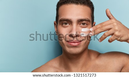 Close up shot of attractive man with healthy skin, applies cream for anti wrinkle or anti aging, cares of body, poses naked or shirtless, isolated over blue background with free space for your text #1321517273