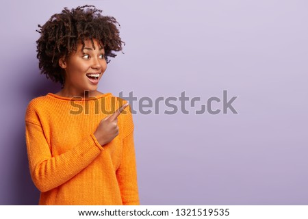 Horizontal shot of attractive dark skinned woman with pleased expression, denomstrates something on free space, points with fore finger at upper right corner, isolated over purple background #1321519535