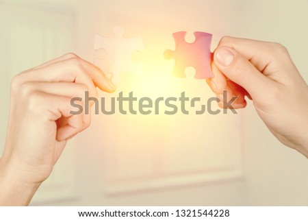 two hands trying to connect couple puzzle piece. with sunset background. symbol of association and connection, business strategy, completing, team support and help concept #1321544228