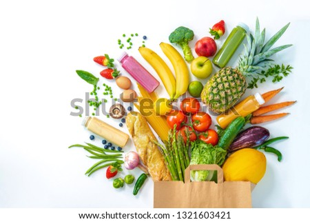 Healthy food selection. Shopping bag full of fresh vegetables and fruits isolated on white #1321603421