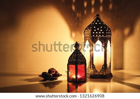 Ornamental Arabic lanterns with burning candles glowing at night. Plate with date fruit on the table. Festive greeting card, invitation for Muslim holy month Ramadan Kareem. Iftar dinner background. #1321626908