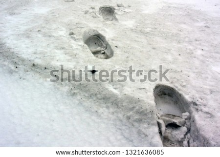 Photo of a snowy background with traces of men's winter boots #1321636085