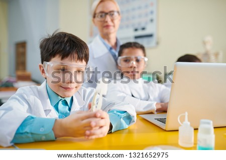 Curious schoolboy in whitecoat holding chemical substance in tweezers while looking at it at lesson of chemistry #1321652975