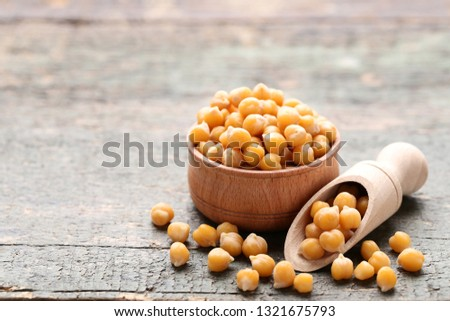 Roasted chickpeas in bowl and scoop on grey wooden table #1321675793