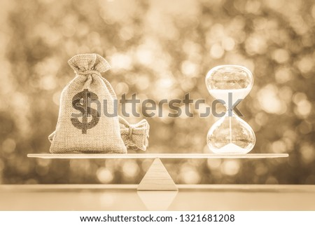 Legacy / inheritance or death tax concept : US dollar money bag, a sand glass or hourglass on a simple balance scale, depicts a tax paid by person who inherits money or property over a period of time #1321681208