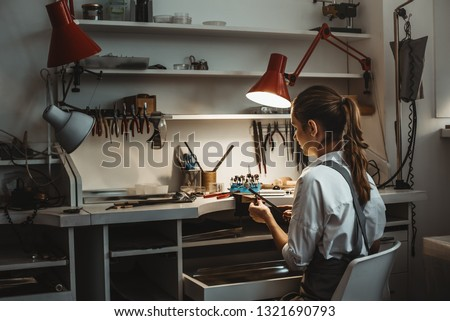 Long work hours. Back view of young female jeweler making new product at her jewelry workshop.