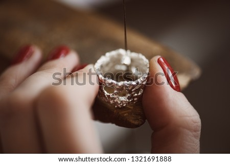 Delicate jewelry work. Close up of a female jeweler's hand working on a ring resizing at her workbench.
