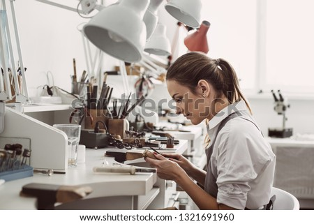 Working all day. Side view of young female jeweler sitting at her jewelry workshop and holding in hands jewelry tools for making accessories #1321691960