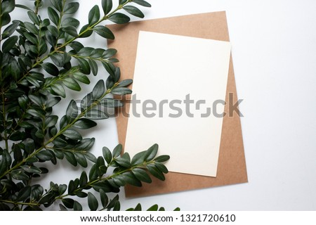 mockup card with plants. invitation card with environment and details Mockup with postcard and flowers on white background. Royalty-Free Stock Photo #1321720610