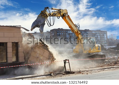 Bulldozer crushing the building at construction site Royalty-Free Stock Photo #132176492