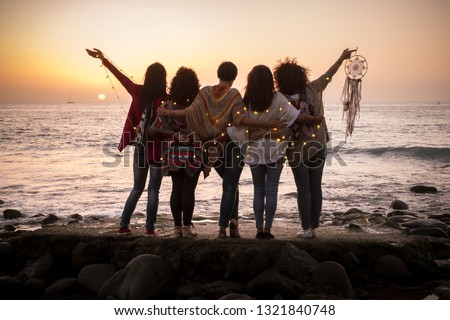 Dreaming image with group of females friends hug each other all together looking the sunset for friendship and love concept - Forever friends and dream lifestyle concept - people enjoying and feeling  Royalty-Free Stock Photo #1321840748