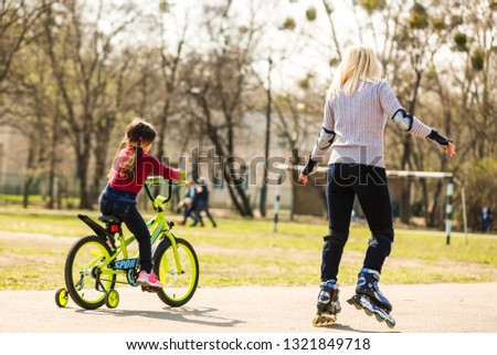 A young mother roller skating. Daughter riding a bicycle #1321849718